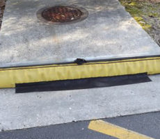 GutterGator installed against curb inlet with weight